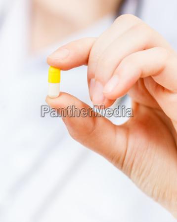 nurse holds pilule in finger