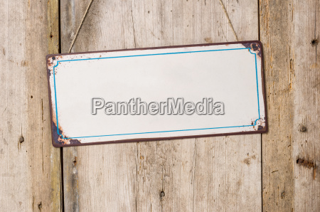 empty metal sign against rustic wooden
