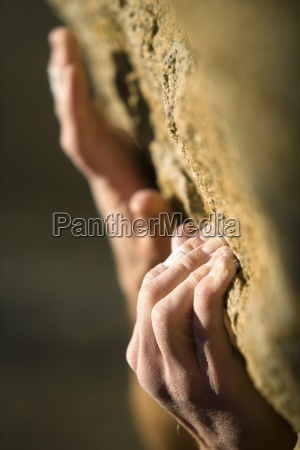 climbers hands gripping onto rock
