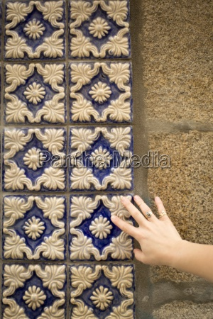 a womans hand touching tiles on