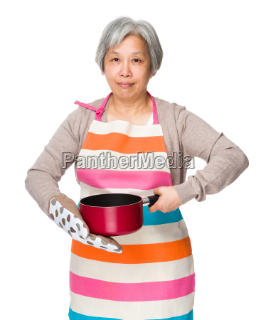 asian housewife hold saucepan with oven