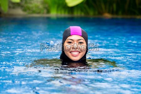 muslim woman wearing burkini swimwear in
