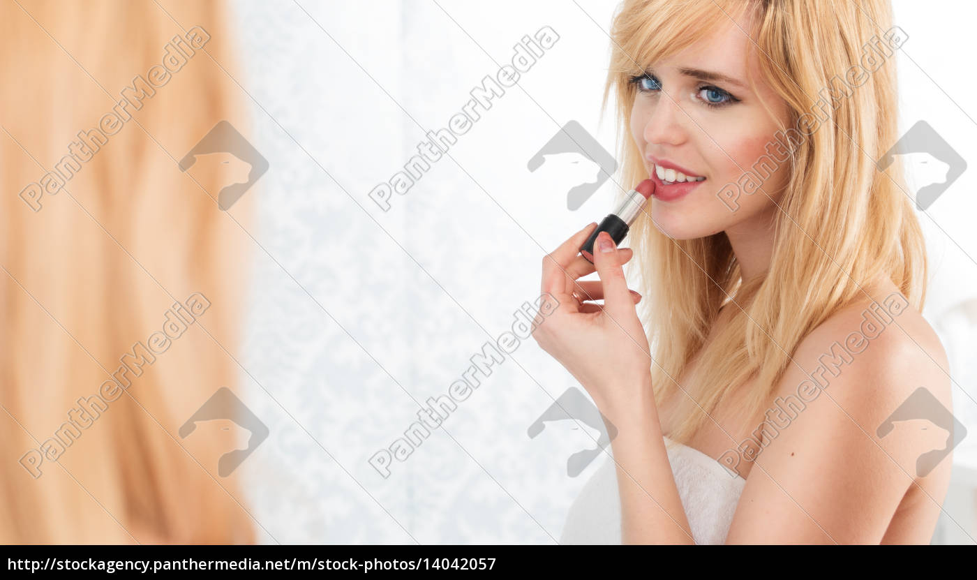 smiling, blond, woman, applying, lipstick, in - 14042057