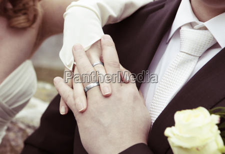 hands with silver wedding rings