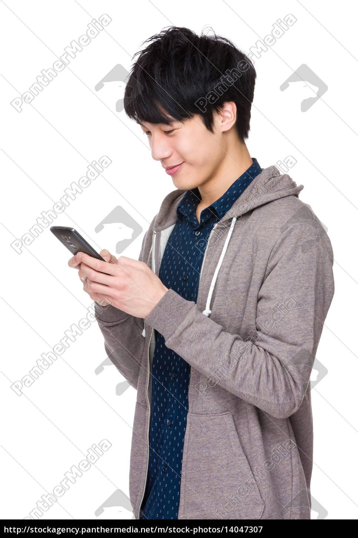 young, asian, man, texting, message, at - 14047307