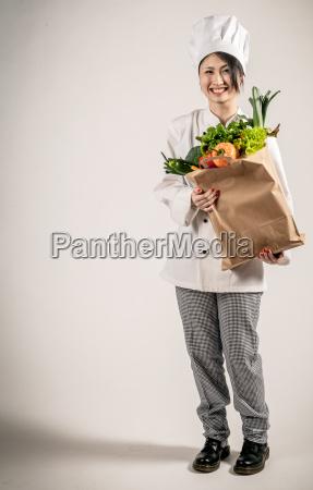 szczesliwy chef posiadajacych papierowa torba ze