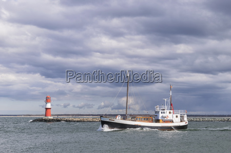 lighthouse of warnemunde with fishing boat
