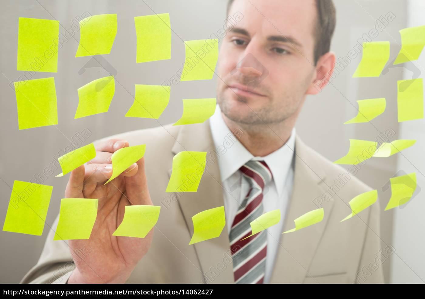 businessman, looking, at, adhesive, notes - 14062427