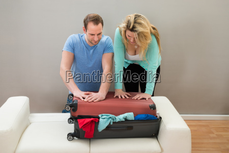 couple, trying, to, close, luggage - 14062535