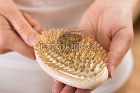 person hand holding comb with loss