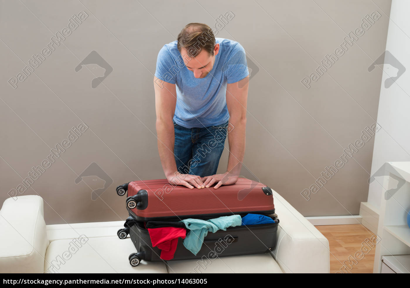 man, trying, to, close, suitcase - 14063005