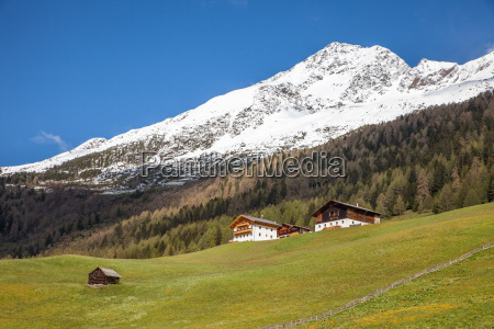 mountain huts and snow capped mountains