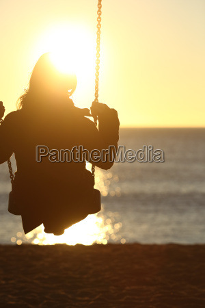 woman silhouette swinging at sunset on