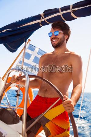 happy, guy, behind, wheel, of, sailboat - 14070753