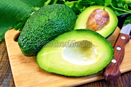 avocado with knife on board