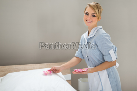 housekeeper, decorating, bed, with, petals - 14079985