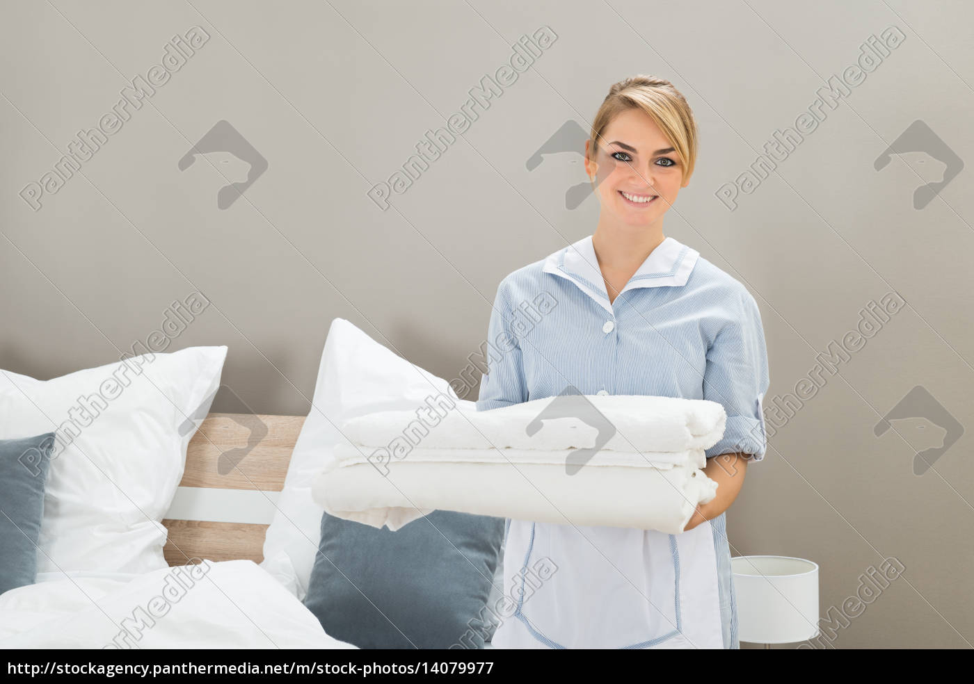 housekeeper, holding, stack, of, sheet - 14079977