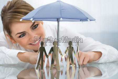 businesswoman, protecting, cut-out, figures, with, umbrella - 14080325