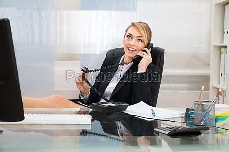 businesswoman, talking, on, landline, phone - 14080203