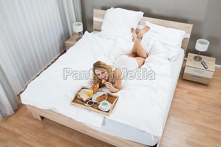 woman, lying, on, bed, having, breakfast - 14083937