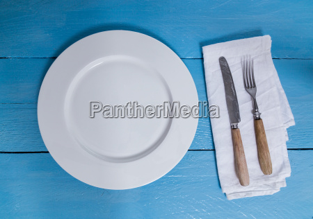 cutlery and plate on blue wooden