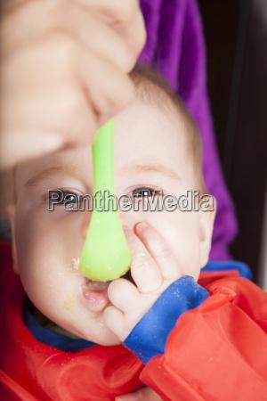 eating green plastic spoon