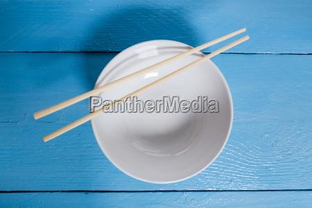 bowl, with, chopsticks, on, blue, wood - 14089771
