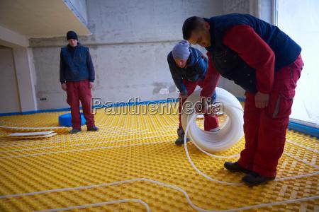 workers, installing, underfloor, heating, system - 14092609