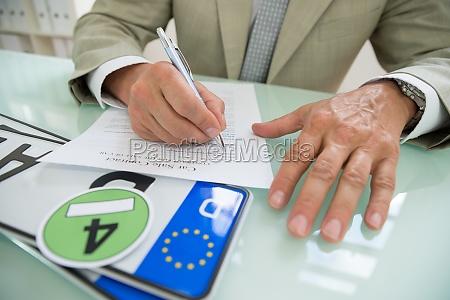 businessman filling car sale contract