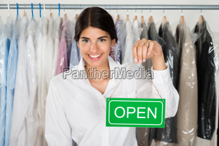 female store owner with open sign