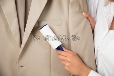 woman cleaning coat with adhesive roller