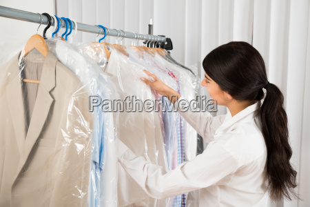 woman looking at clothes in shop