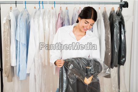 woman holding suit in shop