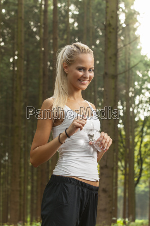 blond woman jogging with water