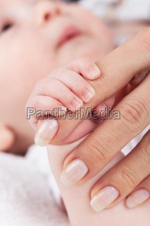 newborn hands holding mothers hand