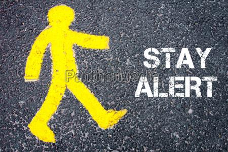 yellow pedestrian figure walking towards stay