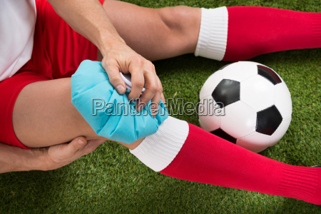 soccer player icing knee with ice