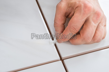 persons hand placing spacers between tiles