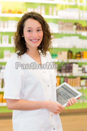 attractive pharmacist using tablet at work