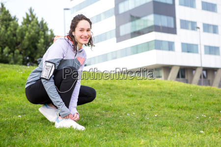 young attractive woman tying shoelaces before