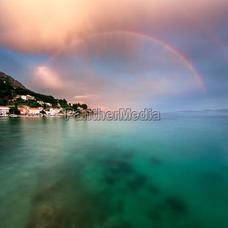 rainbow over rocky beach and small
