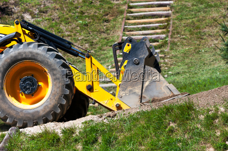 detail yellow excavator traveling on the