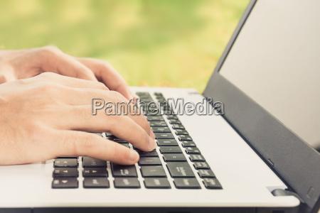 closeup hand using laptop computer outdoor