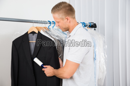 man cleaning dust with lint roller