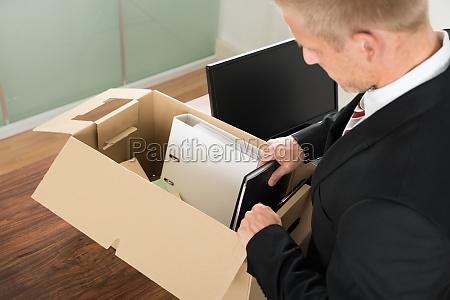 businessman packing files in cardboard box