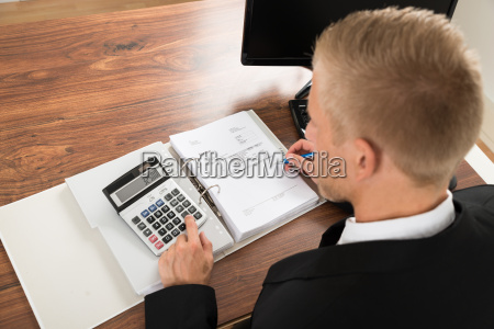businessman calculating invoice at desk in