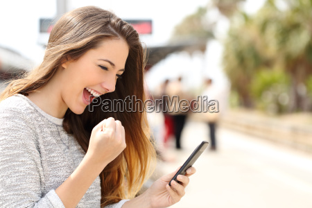 euphoric woman watching her smart phone