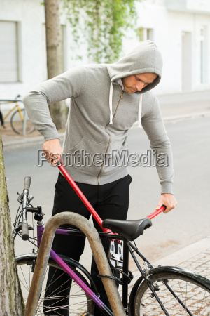 thief trying to break the bicycle