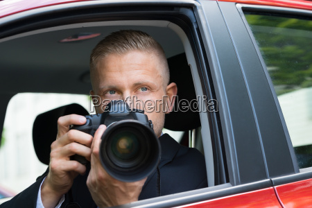 man photographing with slr camera from