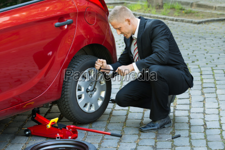 man changing a wheel with spanner